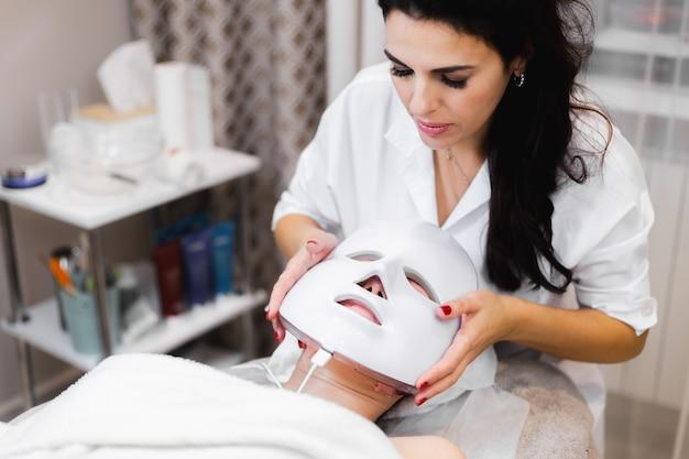 Клиентка лежит в салоне на косметологическом столе с белой маской на лице.
