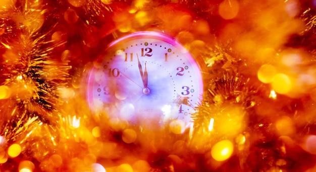 時計の針は新年の到来を示しています。お正月にお祝いの飾りが付いた時計_