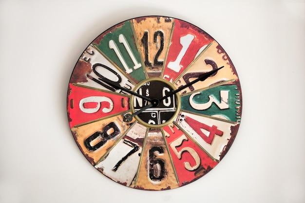 Часы с винтажным металлическим циферблатом на белой стене, отсылающие к дизайну 1930-50-х годов, с цифрами и секторами разных цветов.