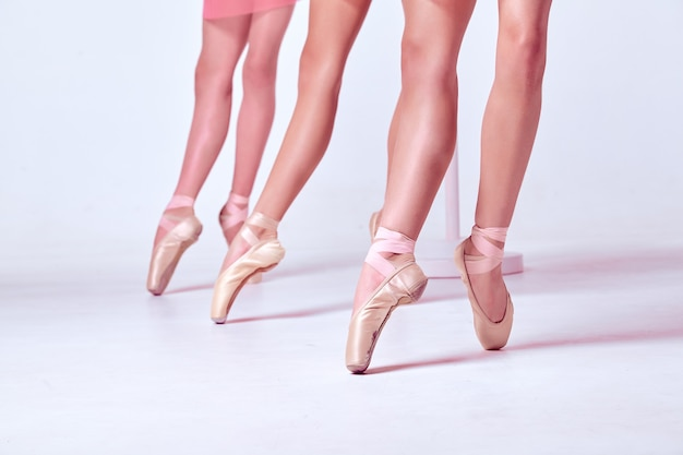 Крупным планом ноги трех молодых балерин в пуантах на бежевом фоне