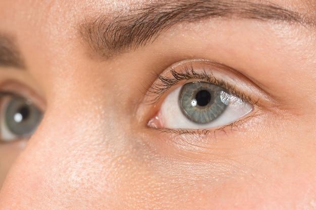 Крупным планом серые глаза на лице молодой красивой кавказской девушки