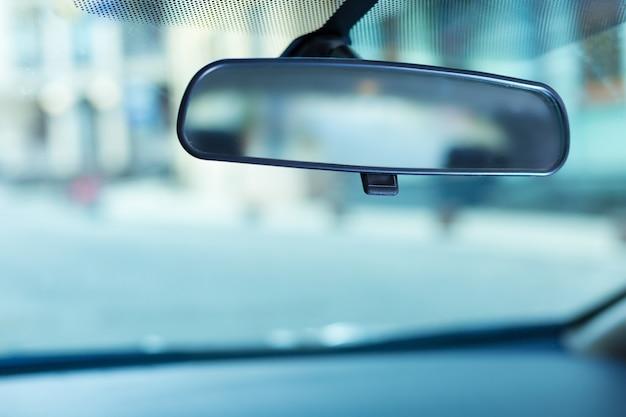 車のきれいなフロントガラスに合わせて調整されている黒い縁のバックミラーのクローズアップ