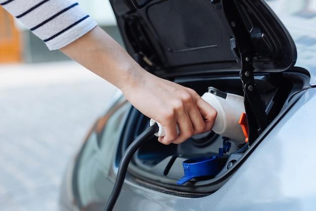전기 노즐을 잡고 전기 자동차를 충전하는 줄무늬 저지의 깔끔한 손 클로즈업
