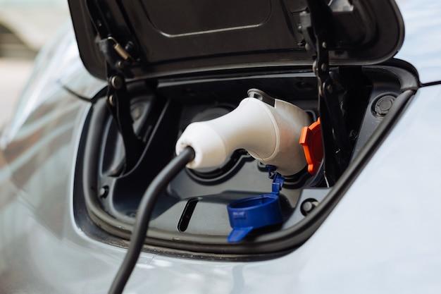Крупный план белого электрического сопла, которое подключается к входному отверстию автомобильного аккумулятора и заряжает электромобиль.