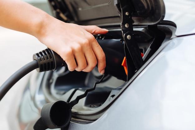 전기 노즐을 잡고 전기 자동차를 충전하는 아름다운 섬세한 여성의 손을 가까이