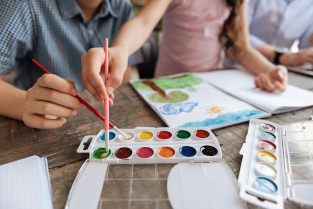 ブラシを持って、リビングルームのテーブルに横たわっている水彩パレットから白と緑の色を選ぶ子供たちの繊細な優しい手のクローズアップ