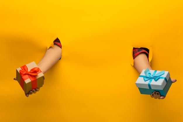 引き裂かれた黄色い紙を通してプレゼントを持っている女性の手のクローズアップ、分離