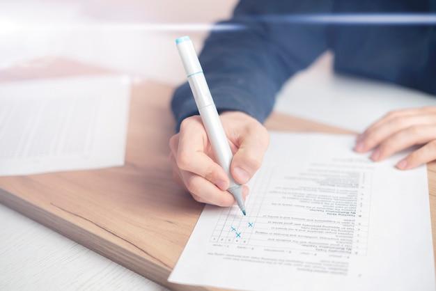 가까운 사람의 손이 종이 시트에 사회 시험에서 답을 쓰는