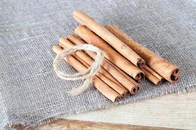 リネンのテーブルクロスに最も近いのは、粗く作られた香りのよいシナモンスティックとバインディング用のロープです