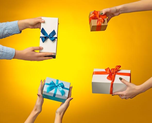 노란색 배경에 선물 상자가 있는 남자와 여자의 손 클로즈업 사진