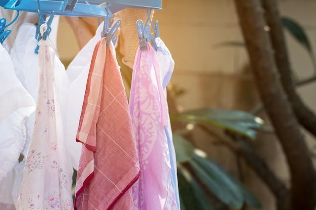 Одежда вешается на стальную рейку для сушки после стирки.