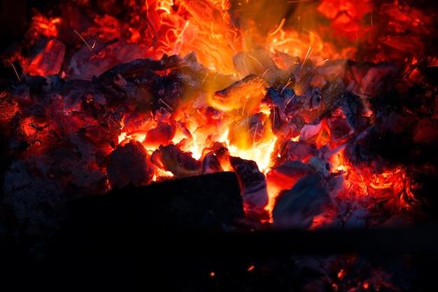 暖炉の中で石炭が明るく燃え、火花が舞い上がり、ストーブの直火が輝きます