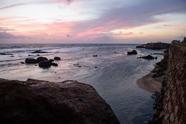 スリランカのゴールの砦の海岸岩の間の素敵な波