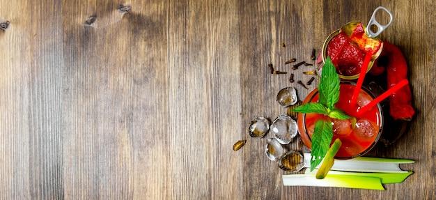 カクテルブラッディマリー。木製のテーブルでアルコール、トマトペースト、その他の材料を使ってカクテルを作る。テキスト用の空き容量。上面図
