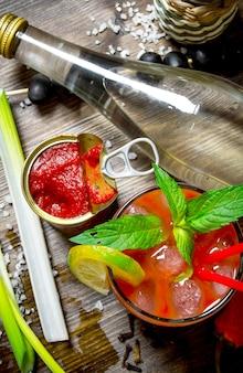 カクテルブラッディマリー。木製のテーブルでアルコール、トマトペースト、その他の材料を使ってカクテルを作る。上面図