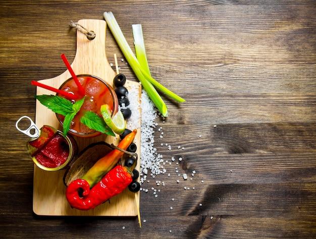 カクテルブラッディマリー。木製のテーブルで食材を使ったカクテル作り。テキスト用の空き容量。上面図