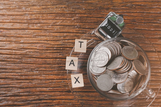 コーヒーカップのコインは木製のテーブルの上に置かれます