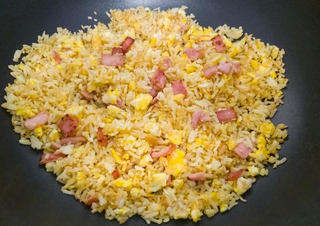 焦げ付き防止の鍋に卵とローストハムを入れたカラフルなチャーハンは、コピースペースの正面にある小さなレストランで提供する準備ができています。