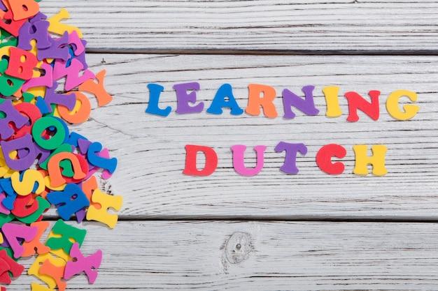 Красочный голландский слова с красочными буквами на белой деревянной доске