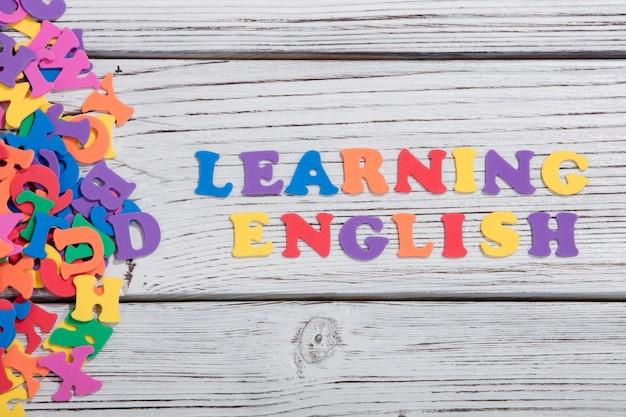 Изучение английского языка с красочными буквами на белой деревянной доске