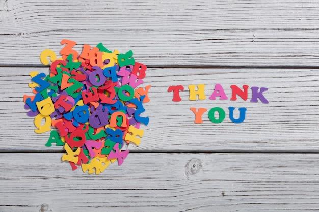 흰색 나무 보드 위에 다채로운 글자로 만든 다채로운 단어 감사합니다.
