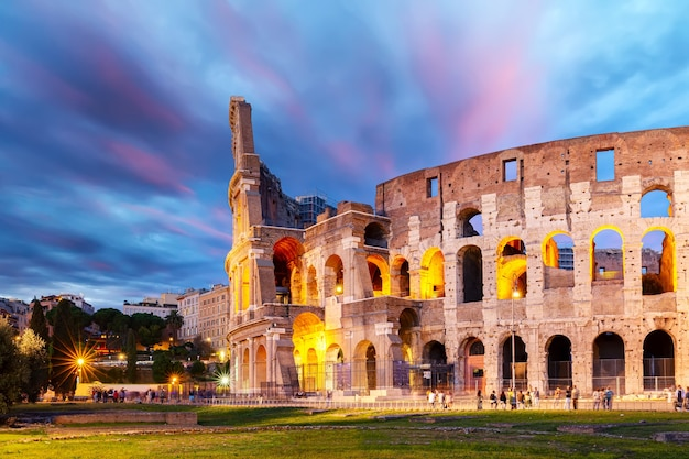 カラフルな夕焼けの夕暮れのイタリア、ローマのコロッセオ。ローマの世界的に有名なコロッセオのランドマーク。