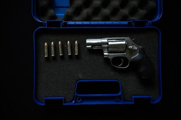 青いスーツケースに弾丸が付いたコンパクトなリボルバーガン