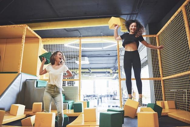 会社は、トランポリンセンターの子供用の遊び場でソフトブロックを楽しんでいる若い女性です。