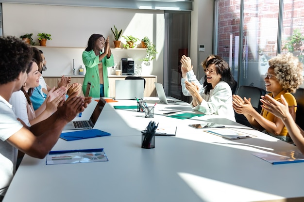 Встреча компании прошла успешно. многорасовая группа коллег хлопает в ладоши на деловой встрече.