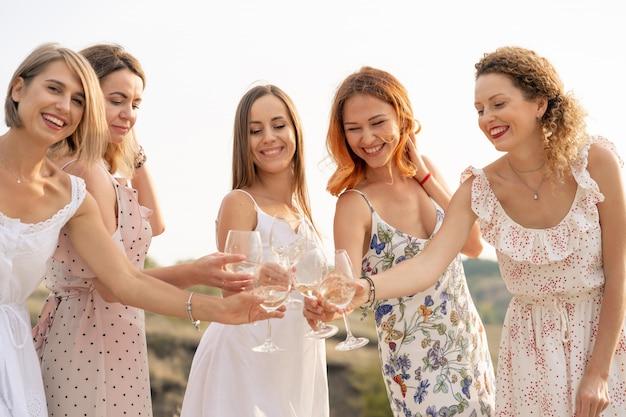Компания подруг наслаждается летним пикником и поднимает бокалы с вином