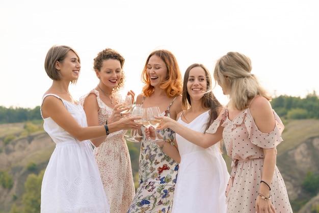 女友達の会社は夏のピクニックを楽しんで、ワインでグラスを育てる