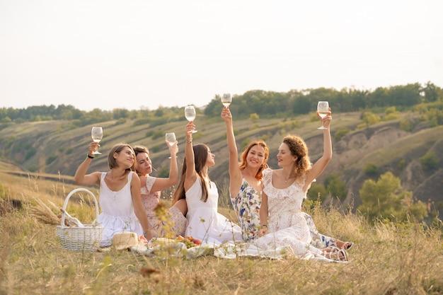 Компания подруг весело проводит время и наслаждается летним пикником на зеленых холмах и поднимает бокалы с вином