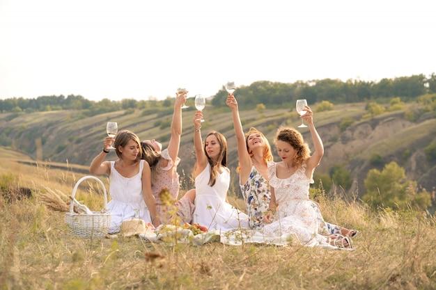 Компания подруг весело проводит время и наслаждается летним пикником с зелеными хлами и поднимает бокалы с вином. концепция людей.