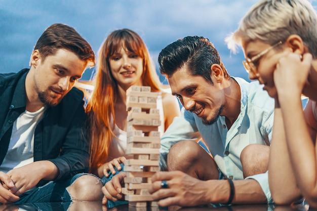 Компания молодых людей, играющих в настольную игру