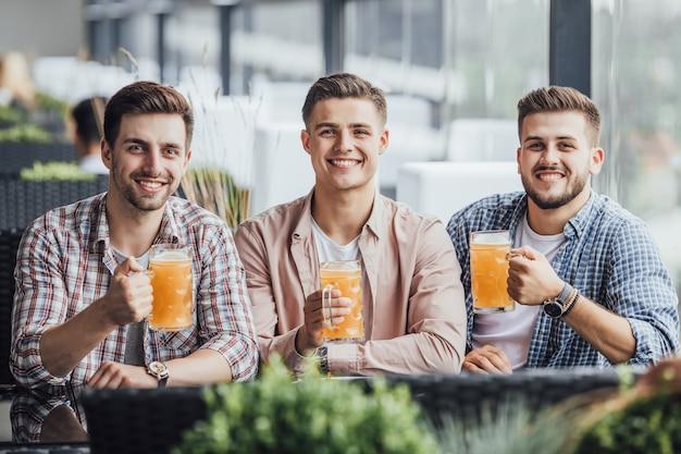 Компания сидит на летней террасе с пивом.