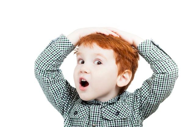 불만을 품은 소년은 밝은 배경에 머리를 잡고 있습니다. 프리미엄 사진