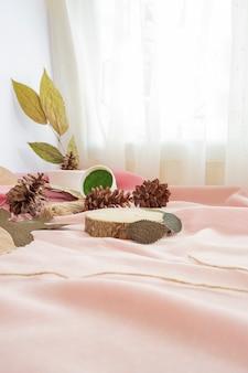 컴포지션은 제품을 표시합니다. 마른 잎과 천으로 장식된 오래된 나무. 제품을 특징으로 하는 미니멀한 구성