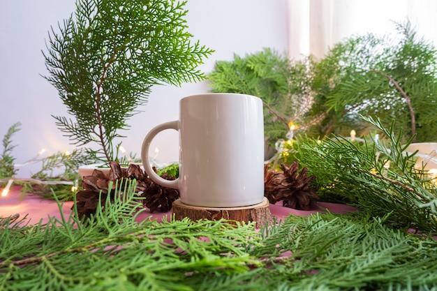 構成は製品を表示します。モミの葉の装飾が施された古い丸い木の上の白いマグカップ。夏の商品展示のアイデア