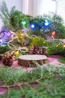 이 구성은 크리스마스와 새해 제품을 특징으로 합니다. 가문비나무 잎 장식이 있는 오래된 둥근 나무. 제품 전시 아이디어