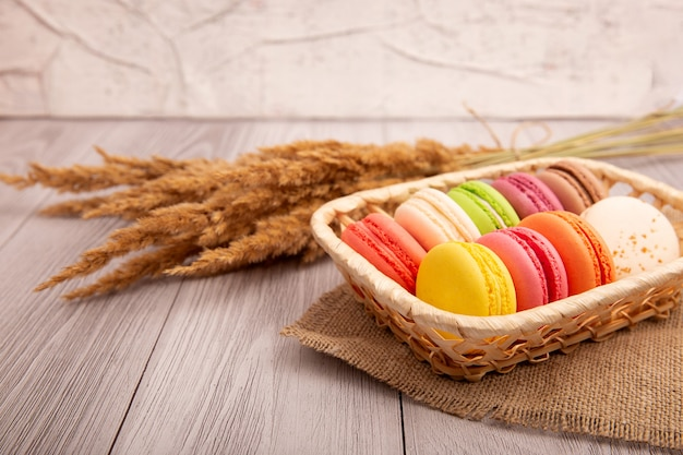 Композиция из французских разноцветных миндальных печений в корзине из ротанга. десерт.