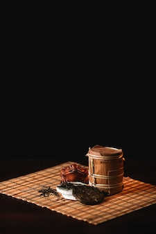 The composition of puer tea with golden toad on a bamboo mat. Black background.