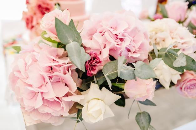 Композиция из фиолетовых, розовых цветов и зелени стоит на сервированном столе в зоне свадебного банкета. закройте вверх.
