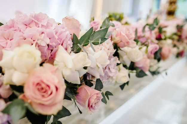Композиция из фиолетовых, розовых цветов и зелени стоит на сервированном столе в зоне свадебного банкета. стол молодоженов подается с посудой и столовыми приборами. закройте вверх.