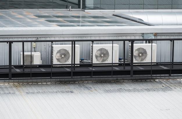 Ряд компрессорных агрегатов системы кондиционирования на крыше современного коммерческого здания, работающий весь день летом, вид спереди с копией пространства.