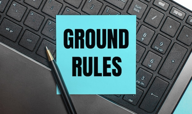 컴퓨터 키보드에는 ground rules 텍스트가있는 파란색 스티커와 펜이 있습니다.