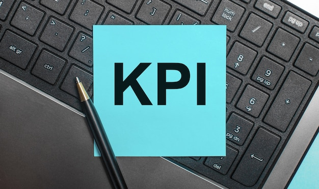 На клавиатуре компьютера есть ручка и синяя наклейка с текстом kpi. плоская планировка.