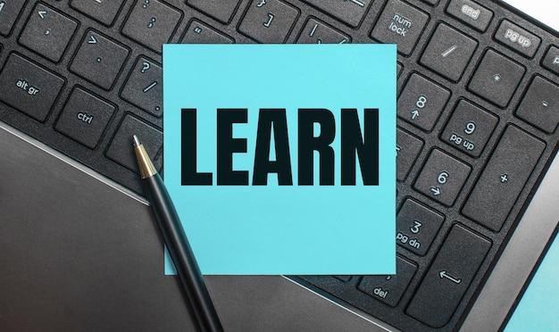 コンピューターのキーボードには、ペンと「learn」というテキストが付いた青いステッカーがあります。フラットレイ。