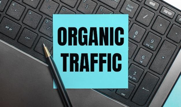 На клавиатуре компьютера есть ручка и синяя наклейка с текстом organic traffic.