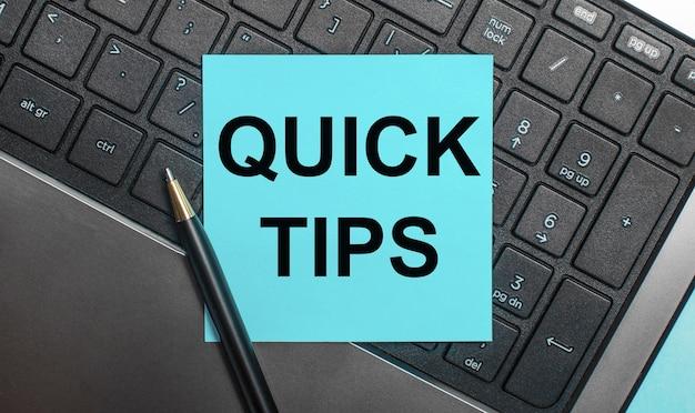 컴퓨터 키보드에는 펜과 quick tips라는 텍스트가있는 파란색 스티커가 있습니다. 평평하다.