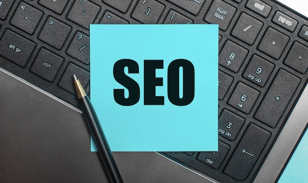 На клавиатуре компьютера есть ручка и синяя наклейка с текстом seo search engine optimization. плоская планировка.